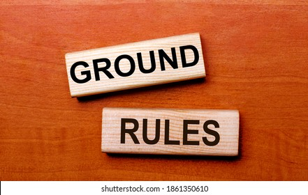 On a wooden table are two wooden blocks with the text GROUND RULES