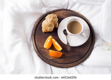 On a wooden tray of coffee with milk and a croissant on the bed., flat lay