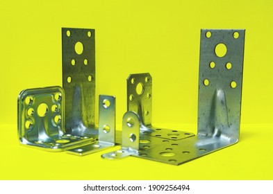 On a yellow background, a close-up of fastening corners for fastening various building materials. - Shutterstock ID 1909256494