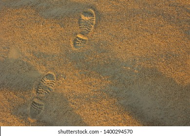 On the yellow sand traces of shoes. Hobo, traveler, pilgrim. View from above.
