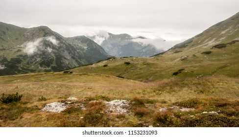on Zavory mountain pass dividing Zadna Ticha and Kobylia dolinka valleys and also Western and High Tatras in Tatra mountains in Slovakia with mountain meadow and peaks during overcast day