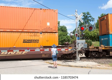 ONALASKA WISCONSIN USA. July 26 2018. Woman waiting at a railway crossing as a BNSF freight train passes by at Onalaska in Wisconsin, USA.