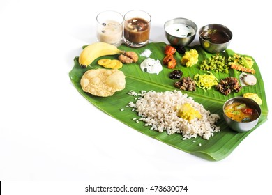 Onam Feast  isolated on white with copy space- Vegetarian meal served in banana leaf on the occasion of Onam festival, selective focus