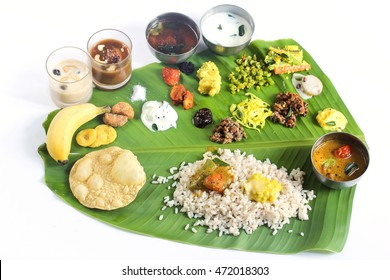 Onam feast on banana leaf isolated on white / South indian Vegetarian meal served in banana leaf, selective focus