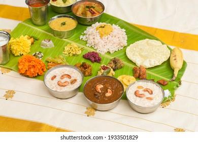 Onam sadhya, Indian women eating with hand boiled rice, served for Kerala Indian festival with curries Sambar, Avial, Thoran, Papadum, Payasam, Banana, Yogurt or Buttermilk, banana chips