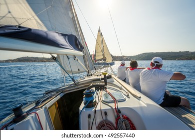 Onboard view of racing sailing yacht with a crew sitting on the starboard side. Sardinia island, Italy.