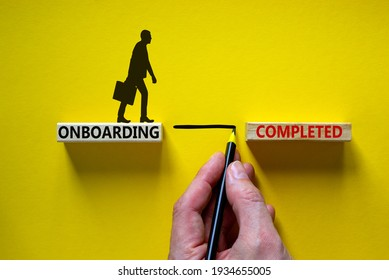 Onboarding completed symbol. Wooden blocks with words 'onboarding completed'. Businessman hand. Beautiful yellow background, copy space. Business and onboarding completed concept.