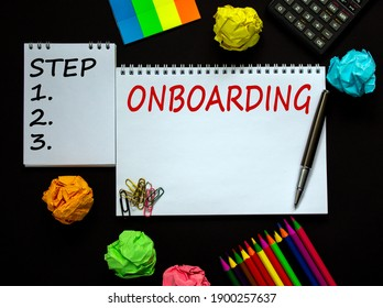 Onboarding symbol. White note with a word 'onboarding' on beautiful black background, colored paper, colored pencils, paper clips, coins and calculator. Business and onboarding concept.