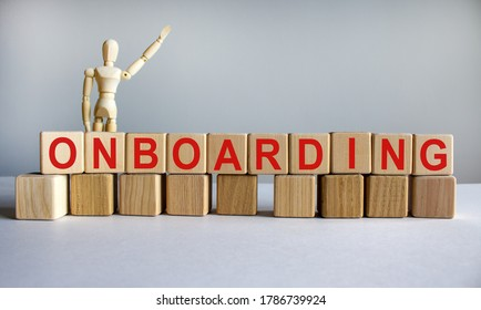 'Onboarding' written on wood blocks. Business concept. Wooden model of human. Copy space.