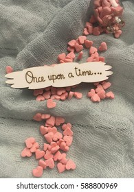 Once upon a time. Concept once upon a time. Once upon a time phrase on grey background with pink sugar hearts.