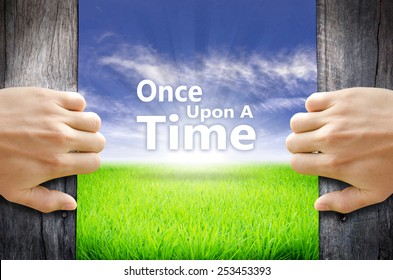 """""""Once upon a time"""" Motivational quotes. Hands opening a wooden door then found a texts floating among new world as green grass field, Blue sky and the Sunrise."""