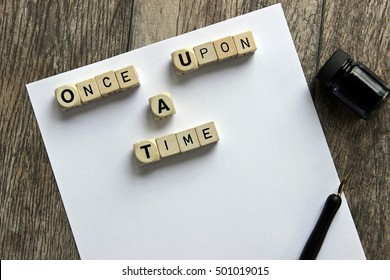 """""""Once upon a time"""" printed on dice against white blank paper with vintage pen and ink over head view to represent writing concept."""