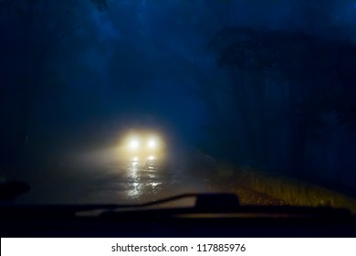 Oncoming cars in the fog on a mountain road. Poor visibility.