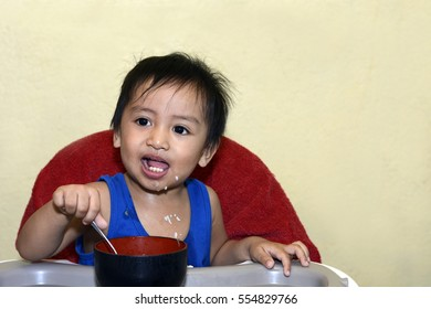 One 1 year old baby boy learning to eat alone smiling happy but messy on baby dining chair at home