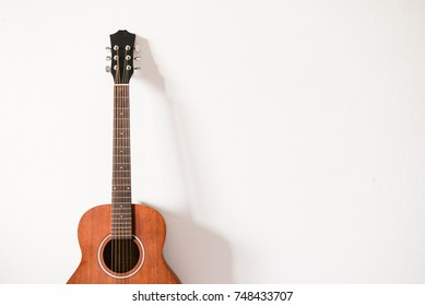 One acoustic guitar rely on the white wall in the room of studio for playing and recording music with copy space