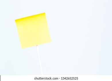 One adhesive yellow paper sticky note for text and blue background. Empty board plank holder with negative space.