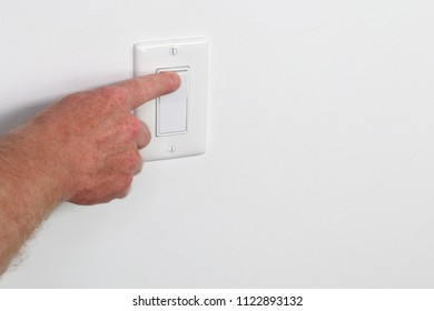 One adult male hand pressing a light switch panel. One flat white panel light switch being turned on Male hand pressing on a flat white wall switch panel from the left to turn on the light in a room.