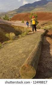 One adult and two children hike along a path near the Painted Hills in Oregon.