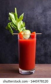 One alcoholic cocktail bloody mary with vegetables and celery on wooden table against black background.