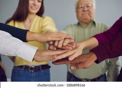 One for all, all for one. Group of diverse young and mature people putting hands together, supporting each other. Unity, common effort, participation, bonding concept. Soft selective focus, close-up