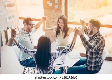 One for all and all for one! Group of excited young people celebrating breakthrough by raising up their hands together , wearing casual clothes sitting by the table in modern nice workstation