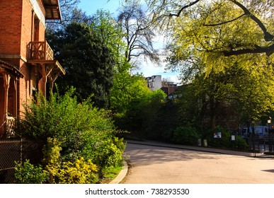 "One of the alley ways in the Butte-Chaumont park in Paris France. On the left of the picture visible on of the nine ""guard's houses"" made of red bricks."