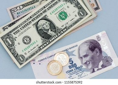 One American dollar and five Turkish Lira banknotes on gray background.