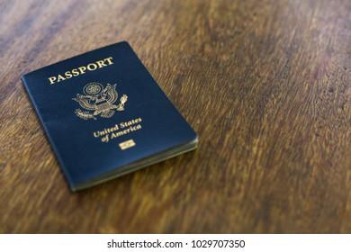 One American passport on a wooden desk
