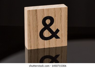 One ampersand symbol block tile on black background with reflection. Love concept.