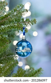One antique blue, silent night, ornament on spruce Christmas tree with lights in the background. Shot with copy space.