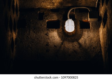One antique flourecent light on weathered interior wall. Confined space, feeling of prison, bunker or mine, negative emotions of claustrophobia and fear