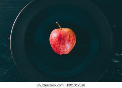 one apple on black plate on dark background, concept of choosing the best organic products