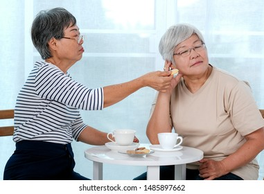 One Asian elderly woman try to reconcile to the other one with cookie during the tea time near balcony in the house.