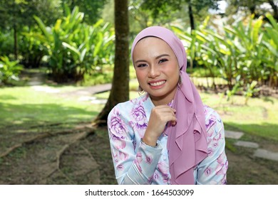 One Asian Malay woman posing smile look forward towards camera confident outdoor green park