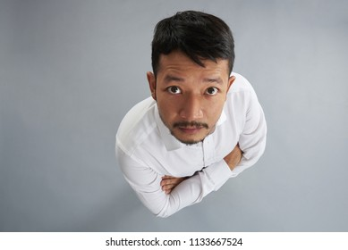 One asian man with crossed arms isolated on gray background above top view
