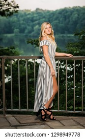 One attractive blonde hair caucasian high school senior posing for senior pictures. Female Teenager portrait standing outdoors at park in summer.