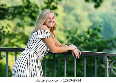 One attractive blonde hair caucasian high school senior posing for senior pictures. Female Teenager portrait outdoors at park in summer.
