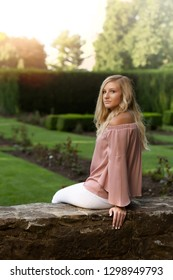 One attractive blonde hair caucasian high school senior posing for senior pictures. Female Teenager portrait outdoors at garden in park during summer.