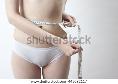 One Attractive Caucasian Girl In White Panties With A Centimeter Measuring Hips And Waist On White