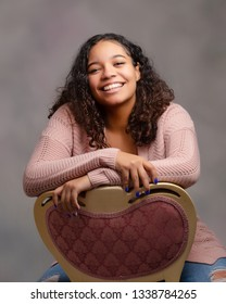 One attractive female biracial teen sitting backwards in chair smiling with perfect teeth posing for senior portraits.
