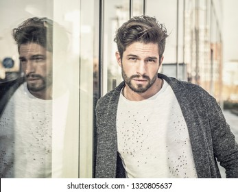 One attractive man in urban environment in city, leaning on glass shop window, wearing cardigan, looking at camera