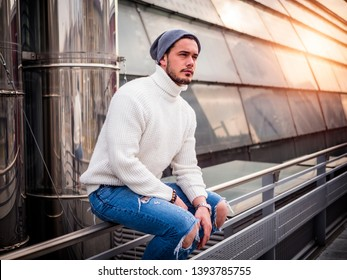 One attractive man in urban setting in modern city, sitting on metal handrail, wearing beanie cap and wool sweater, looking away