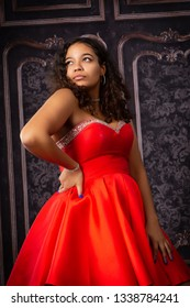 One attractive teenage girl in red prom party dress looking away with one hand on hip.