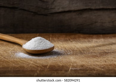 One bamboo spoon filled with white sugar over wooden background with copy space