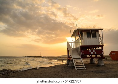 One baywatch lifeguard cabin stand lone in the beach of Doha, Qatar with sunset background