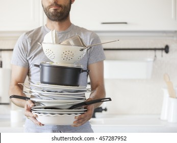 One bearded, unshaven man holds a pile of dirty dishes on the kitchen light background