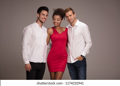 One beautiful african american woman standing with two handsome men, smiling. Elegant style. Studio background.