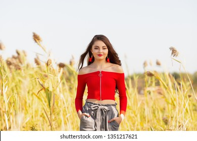 One beautiful female caucasain high school senior girl in red crop top sweater walking outside in a farm field summertime.