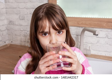 One beautiful Girl drinks water from a glass in the kitchen