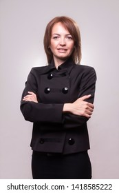 one beautiful mature woman portrait, 40-49 years old, with her arms crossed. Looking at camera. Upper body shot, wearing a simple black dress. Shot in studio, on seamless gray background, isolated.